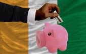 Dollar into piggy rich bank and national flag of cote ivore — Stock Photo