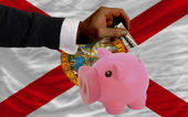 Dollar into piggy rich bank and flag of american state of flori — Stock Photo