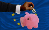 Dollar into piggy rich bank and national flag of europe — Stock Photo