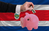 Dollar into piggy rich bank and national flag of costarica — Stock Photo