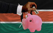 Dollar into piggy rich bank and national flag of kenya — Stock Photo