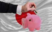Dollar into piggy rich bank and national flag of japan — Stock Photo