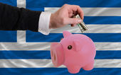 Dollar into piggy rich bank and national flag of greece — Stock Photo