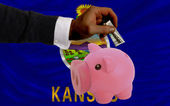Dollar into piggy rich bank and flag of american state of kansa — Стоковое фото