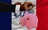 Dollar into piggy rich bank and flag of american state of iowa — Stock Photo