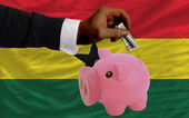 Dollar into piggy rich bank and national flag of ghana — Stock Photo