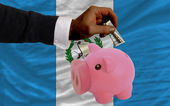 Dollar into piggy rich bank and national flag of guatemala — Stock Photo