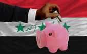 Dollar into piggy rich bank and national flag of iraq — Stock Photo