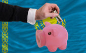 Dollar into piggy rich bank and national flag of kazakhstan — Stock Photo
