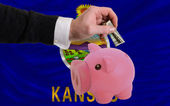 Dollar into piggy rich bank and flag of american state of kansa — Stock Photo