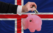 Dollar into piggy rich bank and national flag of iceland — Stock Photo