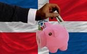 Dollar into piggy rich bank and national flag of dominican — Stock Photo