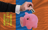 Dollar into piggy rich bank and national flag of mongolia — Stock Photo