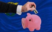 Dollar in piggy rijke bank en vlag van amerikaanse staat van nevad — Stockfoto