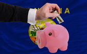 Dollar into piggy rich bank and flag of american state of monta — Stock Photo