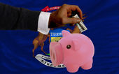 Dollar into piggy rich bank and flag of american state of michi — Stock Photo