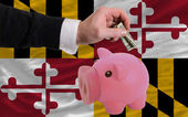 Dollar into piggy rich bank and flag of american state of maryl — Stock Photo