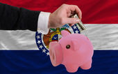 Dollar into piggy rich bank and flag of american state of misso — Stock Photo