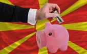 Dollar into piggy rich bank and national flag of macedonia — Stock Photo