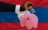 Dollar into piggy rich bank and national flag of laos — 图库照片