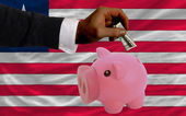Dollar into piggy rich bank and national flag of liberia — Stock Photo