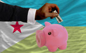 Dollar into piggy rich bank and national flag of of djibuti — Stock Photo