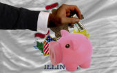Dollar into piggy rich bank and flag of american state of illin — Stock Photo