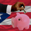 Dollar into piggy rich bank and  national flag of puertorico - Stockfoto