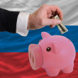 Dollar into piggy rich bank and  national flag of russia - Stock Photo