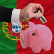 Dollar into piggy rich bank and  national flag of portugal - 图库照片