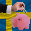 Dollar into piggy rich bank and  national flag of sweden - Photo
