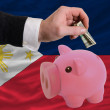 Dollar into piggy rich bank and  national flag of philippines — Stock Photo