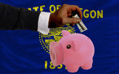 Dollar into piggy rich bank and flag of american state of orego — Stock Photo