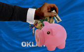 Dollar into piggy rich bank and flag of american state of oklah — Stock Photo