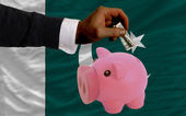 Dollar into piggy rich bank and national flag of pakistan — Stock Photo