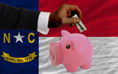 Dollar into piggy rich bank and flag of american state of north — Stock Photo