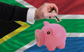 Dollar into piggy rich bank and national flag of south africa — Stock Photo