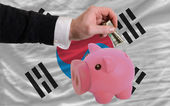 Dollar into piggy rich bank and national flag of south korea — Stock Photo