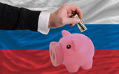 Dollar into piggy rich bank and national flag of russia — 图库照片