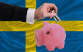 Dollar into piggy rich bank and national flag of sweden — 图库照片