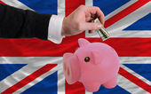 Dollar into piggy rich bank and national flag of united kingdom — Stock Photo