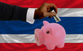 Dollar into piggy rich bank and national flag of thailand — Stock Photo