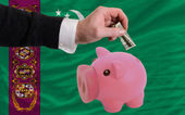 Dollar into piggy rich bank and national flag of turkmenistan — Stock Photo