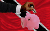Dollar into piggy rich bank and national flag of trinidad tobag — Stock Photo