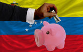 Dollar into piggy rich bank and national flag of venezuela — Stock Photo