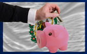 Dollar into piggy rich bank and flag of american state of west — Stock Photo