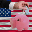 Funding euro into piggy rich bank national flag of america — Stock Photo