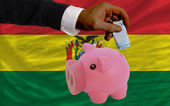 Funding euro into piggy rich bank national flag of bolivia — Stock Photo