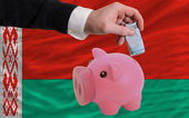 Funding euro into piggy rich bank national flag of belarus — Stock Photo