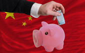 Funding euro into piggy rich bank national flag of china — Stock fotografie
